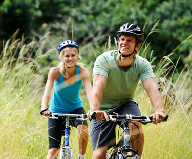 Young couple bike riding through a grassy field