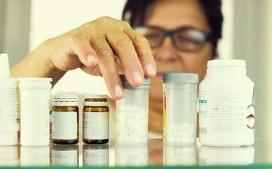 Woman reading prescriptions bottles