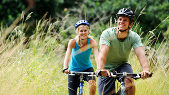 Young couple bike riding through a field