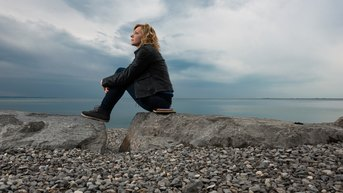 Thoughtful woman sitting on rocks